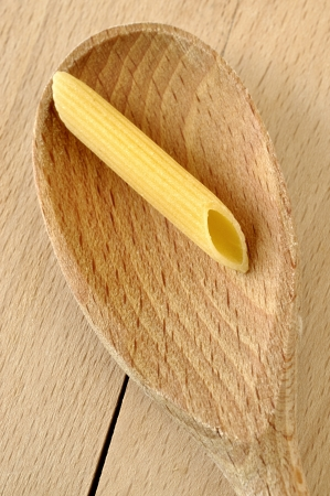 Uncooked penne pasta on a wooden spoon photo