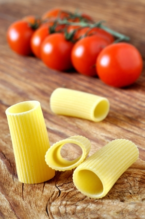 Uncooked rigatoni pasta and cherry tomatoes on a old wooden table photo