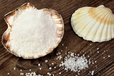 Coarse salt on a scallop shell, wooden background photo