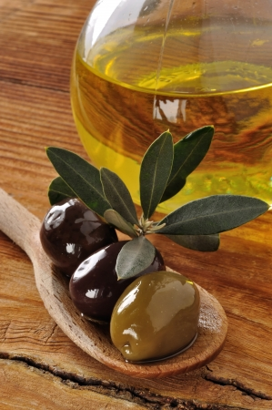 Olives and extra virgin olive oil  on a old wooden table photo