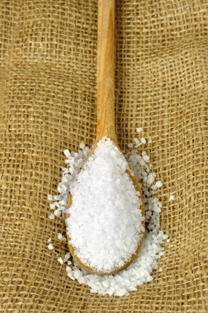 Coarse salt on a wooden spoon, jute background Stock Photo - 17155717