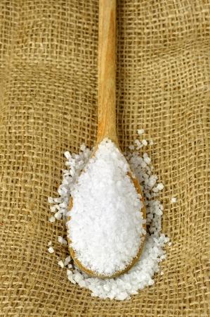 Coarse salt on a wooden spoon, jute background Stock Photo - 17155717