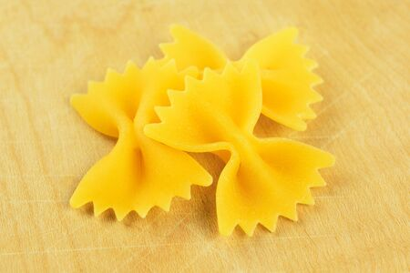 Farfalle, italian raw pasta on a wooden chopping board photo