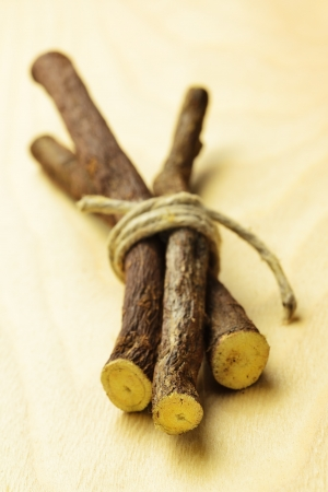 Licorice roots on a wooden table, selective focus Archivio Fotografico