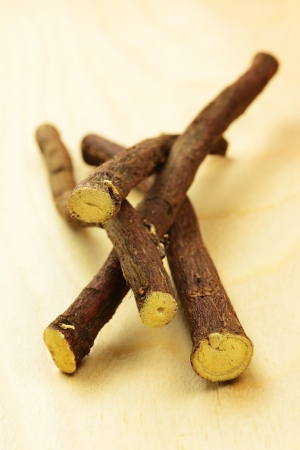 Licorice roots on a wooden table, selective focus Stock Photo