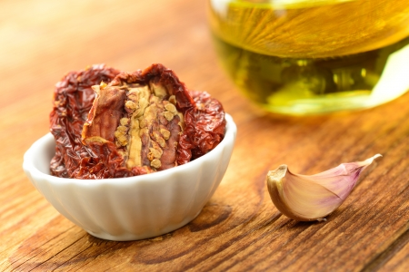 Sun dried tomatoes on a wooden chopping board, selective focus Stock Photo - 17332892