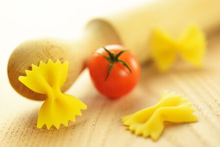 Farfalle, italian raw pasta on a wooden chopping board, selective focus photo