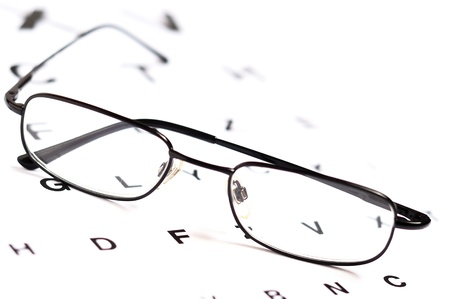 Eyeglasses over eye chart, closeup Reklamní fotografie