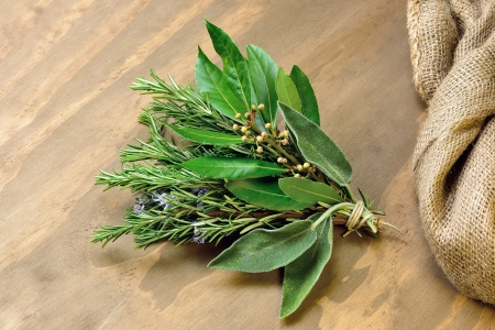 Rosemary, laurel and sage on a old wooden table photo