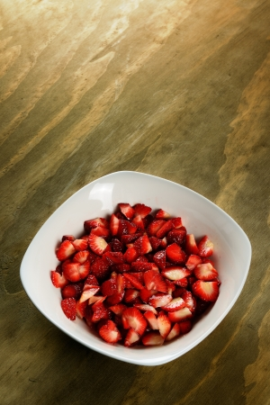 Plátky jahody v misce, dřevěné pozadí