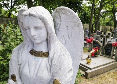 A sculpture of a sad angel walking around the graves of great people.