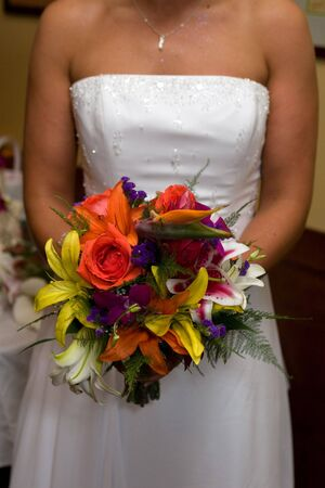 A bride in a white wedding dress holds her bridal bouquet. Stock Photo - 3887228