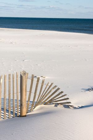 blown: A sandfence is blown over and partly covered by sand at the beach.