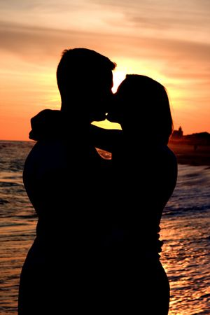 öpücük: The silhouette of a man and woman as they embrace and kiss at the beach.