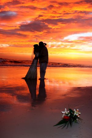 A bride and groom kiss on the beach during a spectacular sunset.
