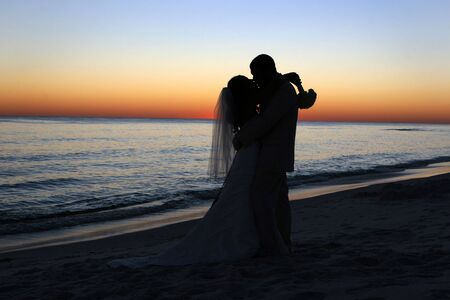 wedding vows: A bride and groom kiss shortly after their wedding vows on the beach.