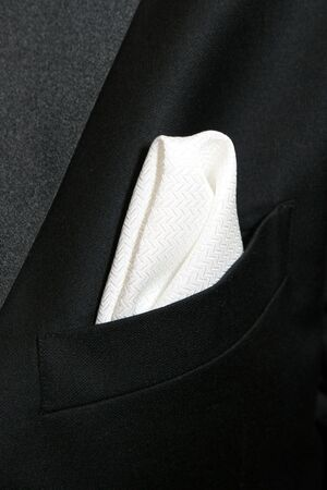 breast pocket: A white textured handkerchief is folded into the breast pocket of a tuxedo.
