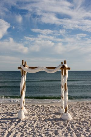 A beach wedding arch is erected on the sand by the sea. photo