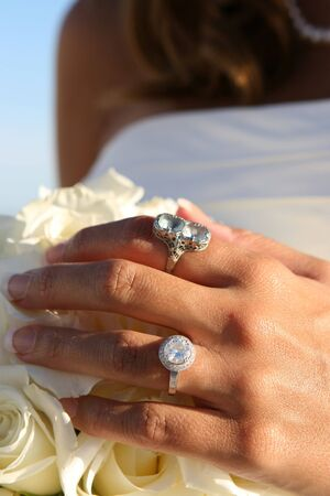adore: Large diamond rings adore a brides hand with flowers. Stock Photo