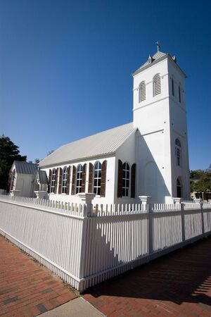 An old country church is surrounded by a white picket fence. Stock Photo - 4036906