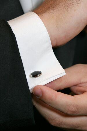 공식적인 복장을 입은 남성이 커프스 링크를 조정합니다.