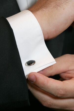 A man in formal attire adjusts his cuff links. Foto de archivo