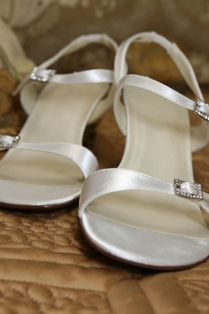 open toe: A pair of white open toe shoes sit on a quilt. Stock Photo
