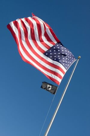 An American flag flaps in the wind against a blue sky along with a smaller POW-MIA flag below. Stock Photo - 4096928