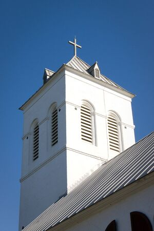 A white cross sits on the top of a church bell tower against a blue sky. Stock Photo - 4096934
