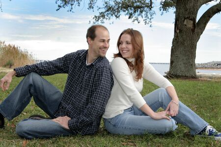 A young married couple having fun in the grass under the trees at a park. Stock Photo - 4088797