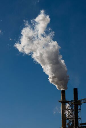 An industrial smokestack at a paper plant spews steam and smoke. Stock Photo - 4121558