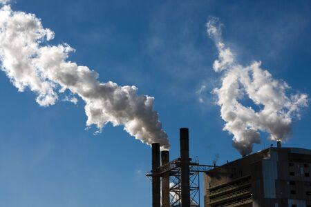 A factory emits smoke and steam into the atmosphere contributing to the green house effect. Stock Photo - 4202787