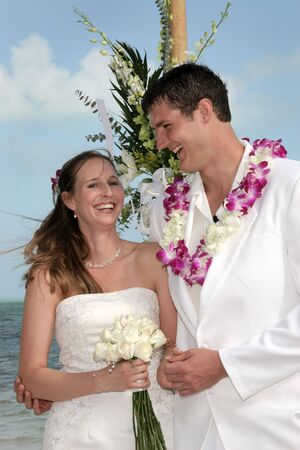A bride and groom enjoy their outdoor wedding ceremony as it takes place on the beach in a tropical setting. Stock Photo - 4192695