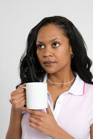 A young African-American woman in a contemplative mood while drinking coffee. Stock Photo - 4192697