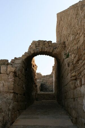 The ruins of an archway crossover a walkway connecting two walls of an structure in the ancient city of Caesarea Maritima, Israel. 版權商用圖片