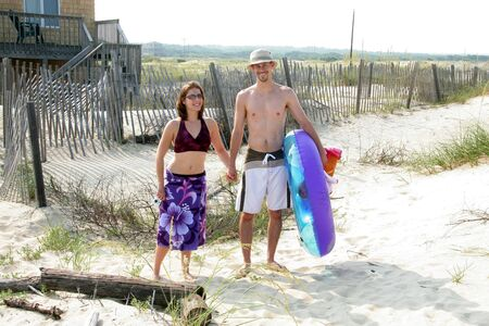 A young adult couple in swim attire are headed to the beach carring inner tube and towels.