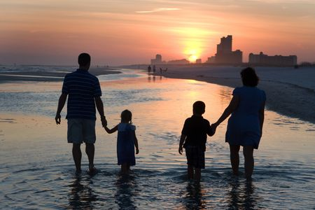 perdido: A young family with children walks in a tide pool as the sun sets on the horizon at the beach.