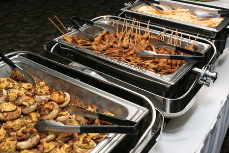 Stuffed mushrooms and skewered chicken sit in a buffet line. Stock Photo
