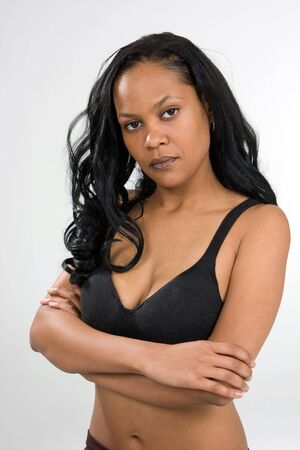 A stern looking, young African-American woman has her arms crossed and is wearing a black sports bra with a look of displeasure. photo
