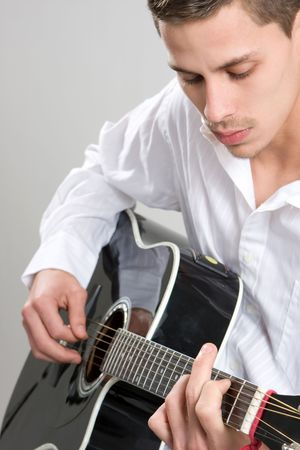 A young man in a white shirt strums an acoustic guitar. Stock Photo - 4296572