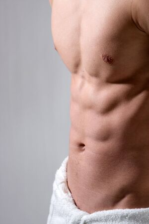 abdominals: A young mans chest is sidelighted with his lower body wrapped in a white towel.