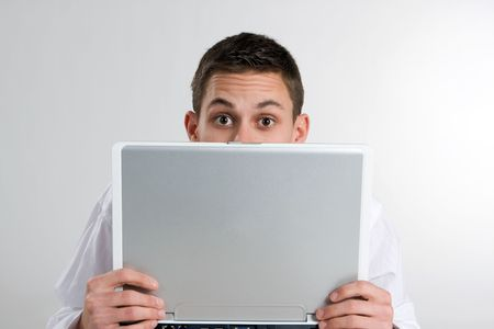 A young man holds a laptop computer closely and peeks over the top with raised eyebrows. Stock Photo - 4296567