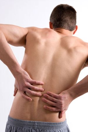 aching muscles: A young man with a backache leans over rubbing his back in pain.