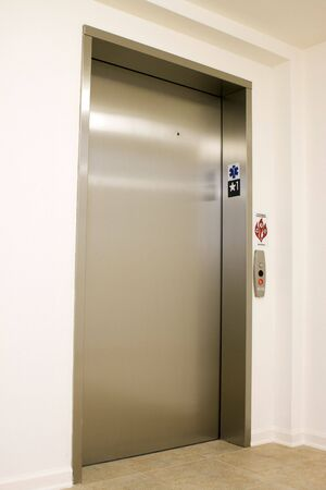 An brushed chrome colored elevator with the door closed waited at level one.