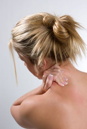 A young adult woman rubs her shoulders in pain. Stock Photo