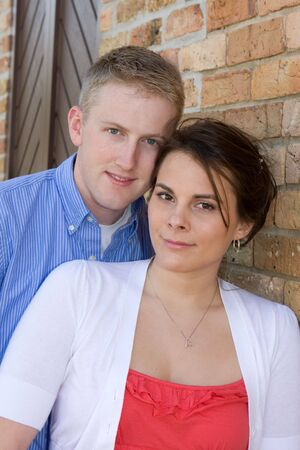 A young adult couple lean against a brick wall smiling.