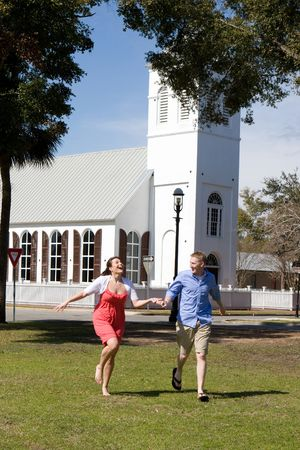 An engaged couple hold hands as they have fun, running by a church.