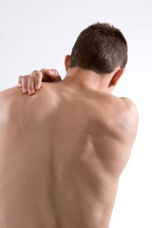 A young man rubs his shoulder in pain. photo