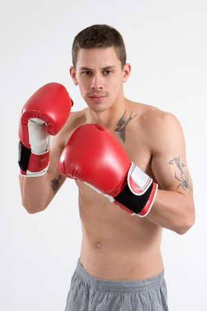 A young tattooed man boxes with red gloves. photo