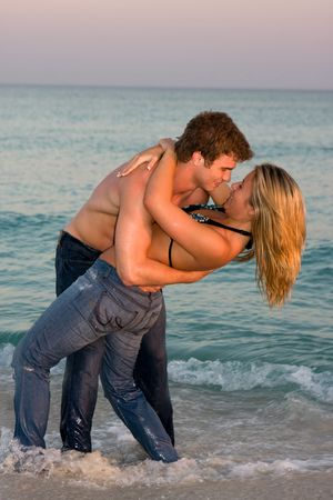 A young couple wearing bluejeans embrace in the surf at sunset. Stock Photo - 4595892
